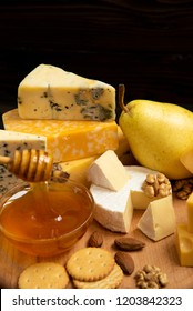 A wooden board with different types of delicious cheese on the table Assorted cheeses on a round wooden board, Camembert cheese,