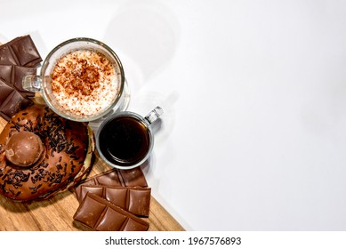 Wooden board with donuts, chocolate, coffee and moccha. Top view