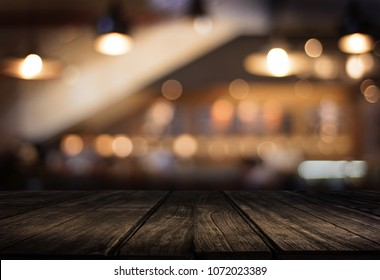 Wooden board empty table  cafe, coffee shop, bar blurred background can be used for display or montage your products and Mock up