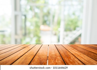 Wooden board empty table in front of blurred background. Perspective light wood over blur in window or door interior- can be used for display or montage your products. Mock up for display of product.