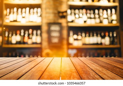 Wooden board empty table in front of blurred background. Perspective light wood over blur wine shelf in night club - can be used for display or montage your products. Mock up for display of product.