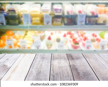 Wooden board empty table in front of blurred background. Perspective light wood over blur in cakes in pastry shop glass display interior- can be used for display or montage your products.
