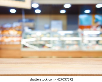 Wooden board empty table in front of blurred background. Perspective light wood over blur in bakery shop - can be used for display or montage your products. Mock up for display of product.