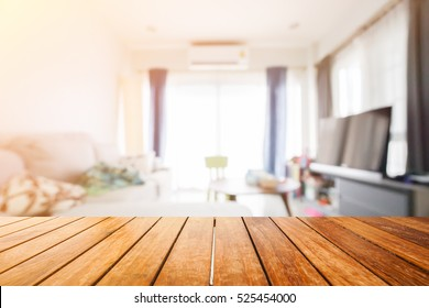Wooden board empty table in front of blurred background. Perspective light wood over blur in living room interior- can be used for display or montage your products. Mock up for display of product.