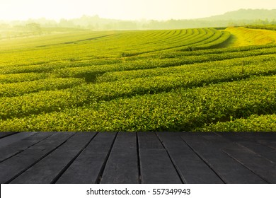 Wooden board empty table in front of tea plantation landscape sunset