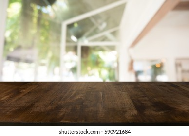 Wooden board empty table in front of blurred background. Perspective white house and  window - can be used for display or montage your products.Mock up for display of product.