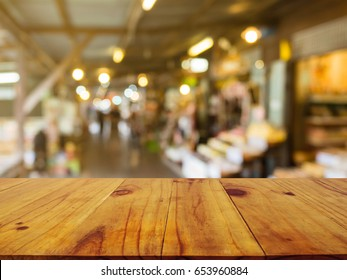 Wooden board empty table in front of blurred background. Perspective brown wood over blur in market or market on street- can be used for display or montage your products.Mock up your products.Vintage
