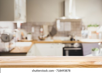 Wooden board empty table in front of Blur image of modern Kitchen Room interior - can be used for display or montage your products.Mock up for display of product.