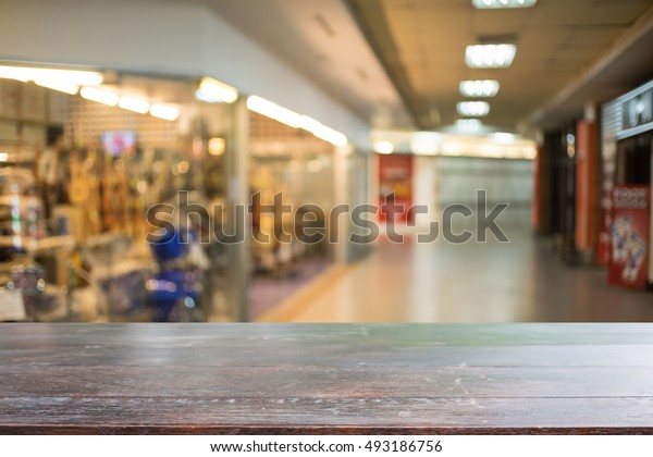 Wooden board empty table in front of blurred background. Perspective light wood over blur in shopping mall - can be used for display or montage