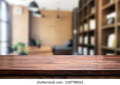 Holzbrett leere Tischplatte und unscharfes Interieur auf unscharfem Hintergrund in der Kaffeebranche, Aufzug für die Produktdarstellung.