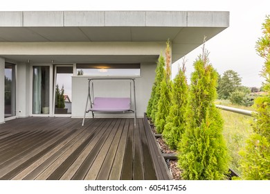 Wooden board floor in spacious outdoor terrace with porch swing