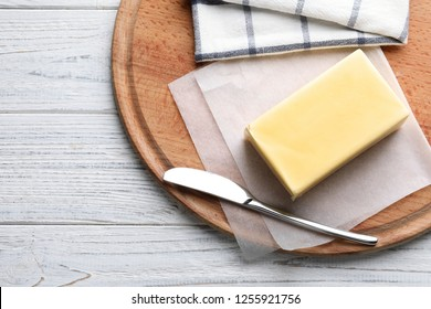 Wooden board with fresh butter and knife on table, top view. Space for text