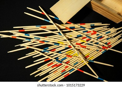 A wooden board game mikado is laid out on a black background. Interesting board game for whole family for the development of motor fingers. Horizontal