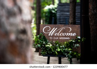 Wooden board with the inscription Welcome to our wedding decorated with green branches