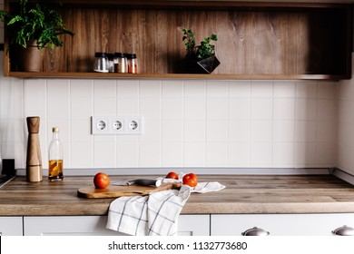 wooden board with knife, olive oil, tomatoes, towel on modern kitchen countertop and shelf with spices and plants. cooking food. Stylish kitchen interior design in scandinavian style