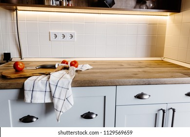 wooden board with knife, tomatoes, towel on modern kitchen countertop and shelf with spices and plants. cooking food. Stylish kitchen interior design in scandinavian style