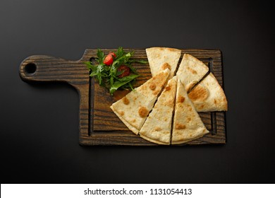 Wooden board with lavash and salad isolated on a black background.