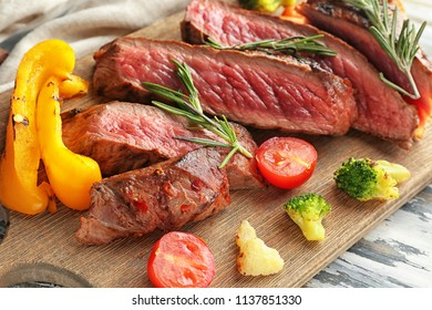 Wooden board with meat and vegetable garnish on table, closeup
