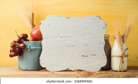 Wooden board, milk bottle and fruits on table. Jewish holiday shavuot concept.