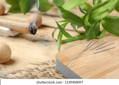 Wooden board with needles for acupuncture on table, closeup