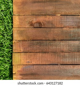 A wooden board on green grass, a template for picnic-related design, overhead shot, square photo