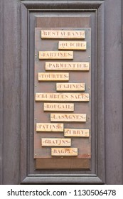 Wooden board on a restaurant with names of french dishes