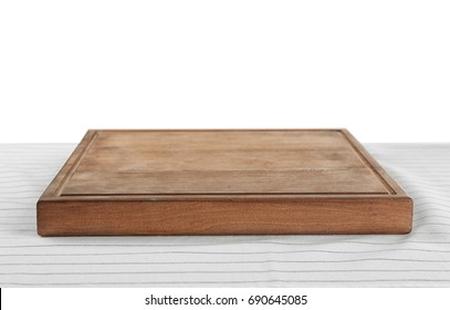 Wooden board on tablecloth against white background