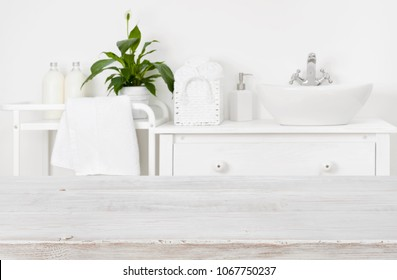 Wooden board over blurred bathroom interior background with copy space