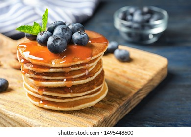 Wooden board with pancakes, syrup and blueberries on table, closeup