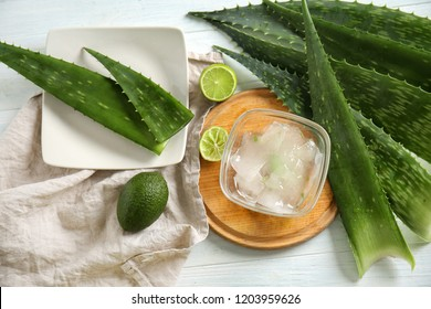 Wooden board with peeled aloe vera and exotic fruits on white table