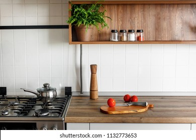 wooden board with pepper mill, knife, tomatoes on modern kitchen countertop and shelves with spices in glass jars. cooking food. Stylish gray kitchen interior  design in scandinavian style