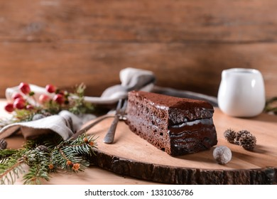 Wooden board with piece of tasty chocolate cake on table