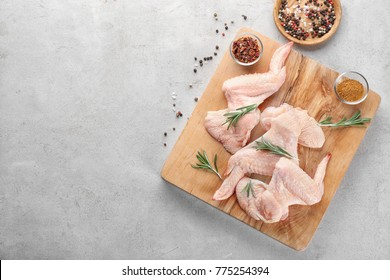 Wooden board with raw chicken wings on grey background