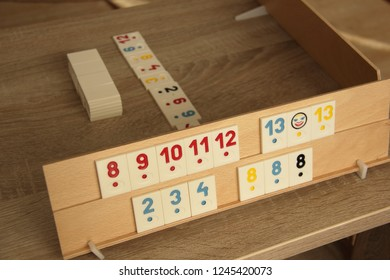 Wooden board with sets of numbers. Rummy game