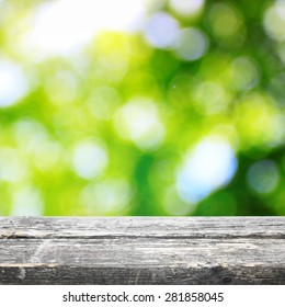 Wooden board table with bokeh summer background