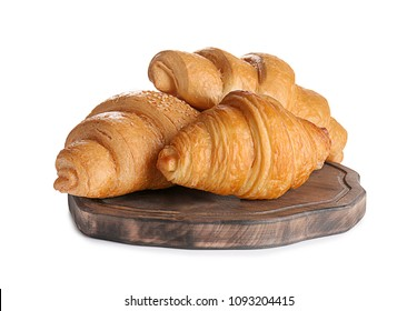 Wooden board with tasty croissants on white background