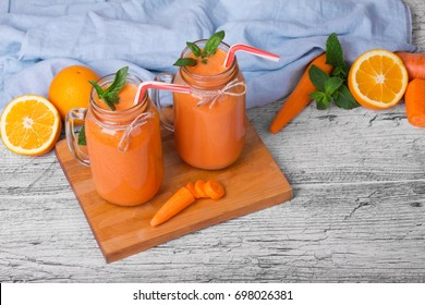 A wooden board with two mason jars with carrot smoothie, basil, oranges anf leaves of mint on a light background.