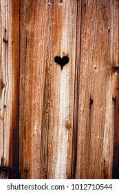 Wooden boards background. Old window shutter with cut out heart.