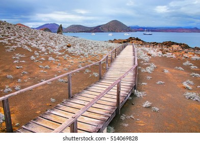 Wooden boardwalk on Bartolome island in Galapagos National Park, Ecuador. The island consists of an extinct volcano and a variety of red, orange, green, and glistening black volcanic formations.