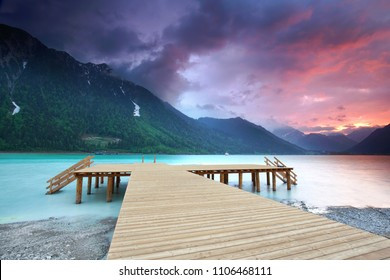wooden boardwalk on the lake, turquoise water on mountain lake and purple sunset on sky