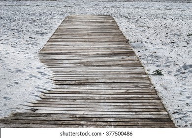 wooden boardwalk on the sand at sunset