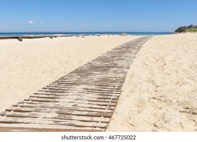 Wooden boardwalk path through the sand on the beach.