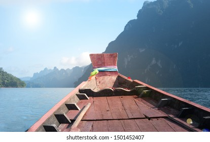 Wooden boat bow in the at with mountian background, Ratchaprapha Dam at Khao Sok National Park, Surat Thani, Thailand.