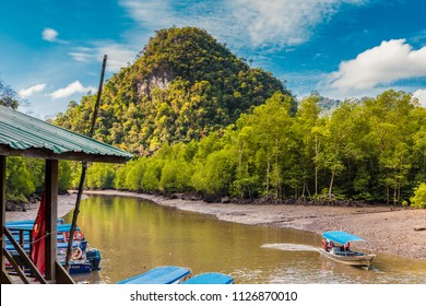 A wooden boat dock and moored motorboats in front of a beautiful limestone hill at the Kilim Jetty, located at the north eastern edge of Langkawi on Kilim river, Malaysia. One motorboat is returning.