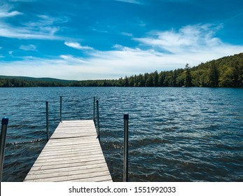 Wooden boat dock on a blue sky summer day in southern New Hampshire.