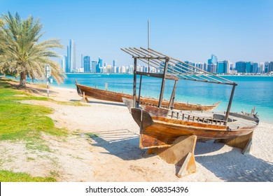Wooden boat at the Heritage Village, in front of the Abu Dhabi skyline, United Arab Emirates