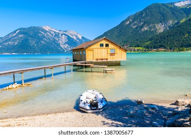 Wooden boat house and pier of shore of beautiful Achensee lake on sunny summer day, Tirol, Austria