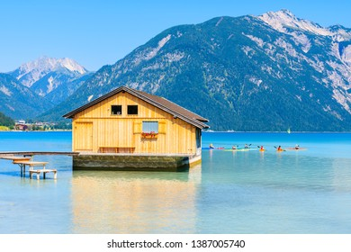 Wooden boat house and tourists on kayaks on beautiful Achensee lake on sunny summer day, Tirol, Austria