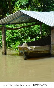 A wooden boat is moored under a make-shift shelter on a muddy branch of the Mekong River. The shelter has a corrugated iron roof. Trees cover the water's edge.