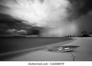 wooden boat near the beach during storm, located at fisherman village Terengganu,long exposure shot. black and white photography. soft and grain effect.